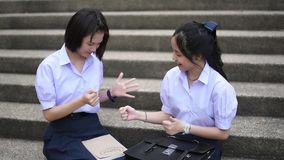 Cute Asian Thai high schoolgirls student couple in school uniform are having fun playing `rock-paper-scissors` with her student fr. Iend stock video