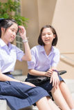 Cute Asian Thai high schoolgirls student couple in school uniform sit on the stairway chatting with a happy smiling and laughing f Royalty Free Stock Image