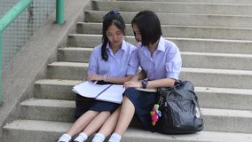 Cute Asian Thai high schoolgirls student couple in school uniform sit on the stairway discussing and reading homework or exam. Together stock video