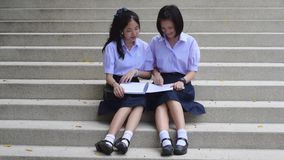 Cute Asian Thai high schoolgirls student couple in school uniform sit on the stairway discussing and reading homework or exam. Together with happy expression stock video footage