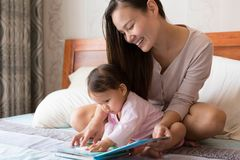Cute asian toddler being read to by her young mother. stock images