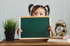 Cute asian toddler holding a blank chalkboard for copy space text royalty free stock image