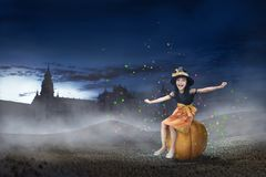 Cute asian witch girl sitting on the pumpkin stock photos