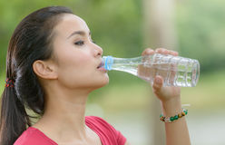 Cute asian woman drinking water on nature background Royalty Free Stock Image