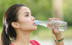 Cute asian woman drinking water on nature background Royalty Free Stock Photography