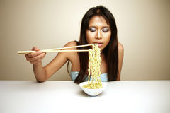 Cute Asian woman eating noodles Royalty Free Stock Photography