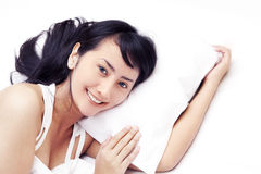 Cute Asian woman smiling on bed. Beautiful Asian woman smiling on bed shot in studio isolated on white with copy space Royalty Free Stock Photos