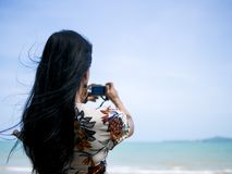 Cute asian woman wearing retro dress standing at seaside holding camera in hand and take a photo royalty free stock photography
