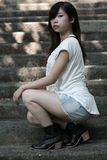Cute Asian woman in a white top looking at viewer with attitude. Beautiful Asian woman wearing a white top squatting down on steps looking at viewer with a cool stock image