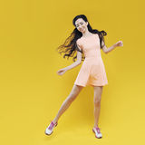 Cute asian young girl waving to someone. Portrait on yellow background. Stock Photos