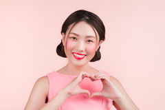 Cute asian young woman with fashion makeup gesture hand making h Stock Photos