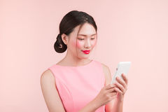Cute asian young woman with fashion makeup holding smartphone an stock photography