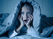 Beautiful little girl awake from a nightmare afraid and suffering fear of dark royalty free stock photos