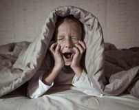 Beautiful little girl awake from a nightmare afraid and suffering fear of dark stock photos