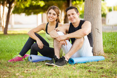Cute athletic couple at a park. Portrait of a young Hispanic couple with yoga mats sitting next to a tree in a park Royalty Free Stock Images