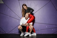 Cute athletic couple. Slender beautiful girl and strong athletic man in sports clothes are hugging on the background of royalty free stock photography