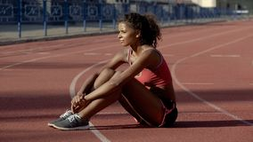 Cute athletic girl tired after workout at stadium sitting on track, resting stock image