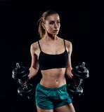 Cute athletic model girl in sportswear with dumbbells in studio against black background. Ideal female sports figure. Stock Photography
