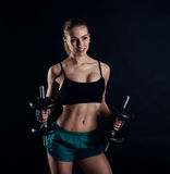 Cute athletic model girl in sportswear with dumbbells in studio against black background. Ideal female sports figure. Royalty Free Stock Photos