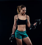 Cute athletic model girl in sportswear with dumbbells in studio against black background. Ideal female sports figure. Stock Photos