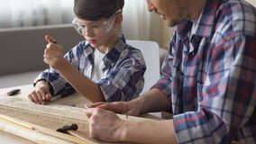 Cute attentive boy working with screwdriver and wood, father teaching son. Stock footage stock video