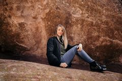 Young Cute Modern Caucasian Woman Smiling in Front of Massive Natural Red Rock Stone Wall Outside in Nature at the State Park stock photography