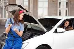 Cute attractive girl examining car engine at the auto repair royalty free stock image