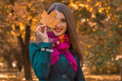 Cute attractive girl in pink scarf keeps the sheet near the eyes and smiles Royalty Free Stock Photos