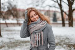 Cute attractive pretty young woman in gray gloves in a trendy gray coat with a vintage knitted scarf is standing and smiling royalty free stock photography