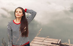 Cute attractive young woman enjoying harmony of nature on pier n Stock Photos