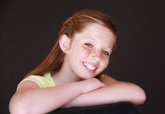 Cute Auburn Haired Girl. Cute tween aged girl with auburn hair and freckles against a black backdrop Stock Image