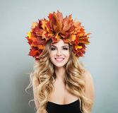 Cute autumn woman. Beautiful female model in colorful fall leaves, makeup and curly haircut.  royalty free stock photo