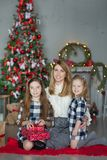 Cute awesome blond mother mom with two girls daughters celebrating New Year Christmas close to xmas tree full of toys in stylish d Royalty Free Stock Photos