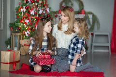 Cute awesome blond mother mom with two girls daughters celebrating New Year Christmas close to xmas tree full of toys in stylish d Stock Photo