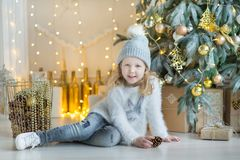 Cute awesome girl celebrating New Year Christmas close to xmas tree full of toys in stylish dresses with candies Royalty Free Stock Image
