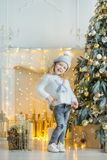 Cute awesome girl celebrating New Year Christmas close to xmas tree full of toys in stylish dresses with candies Royalty Free Stock Images