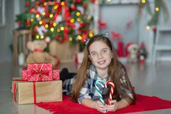 Cute awesome girl celebrating New Year Christmas close to xmas tree full of toys in stylish dresses with candies Stock Images