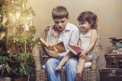 Cute babies boy and girl in a chair reading a book in a interior Royalty Free Stock Image