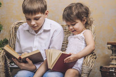 Cute babies boy and girl in a chair reading a book in a interior Royalty Free Stock Photos