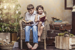 Cute babies boy and girl in a chair reading a book in a interior Stock Image