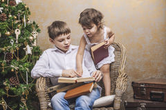 Cute babies boy and girl in a chair reading a book in a interior Stock Photos
