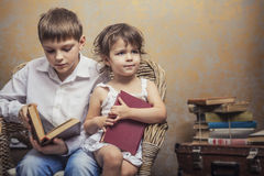 Cute babies boy and girl in a chair reading a book in a interior Royalty Free Stock Images