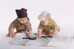 Cute babies planning travel with map Royalty Free Stock Photo