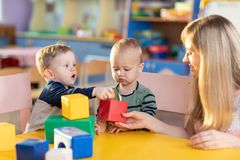 Cute babies play with blocks. Educational toys for preschool and kindergarten child. Little boys build block toys at royalty free stock photo