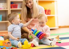 Cute babies play with carer indoors. Cute babies play with carer in nursery or kindergarten royalty free stock photos