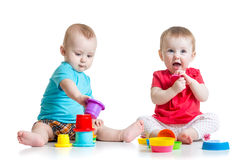 Cute babies playing with color toys. Children girl. Two cute babies playing with cup toys. Children toddlers girl and boy sitting on floor, on white background royalty free stock photos