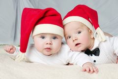 Cute babies with santa hats. On bright background royalty free stock photos
