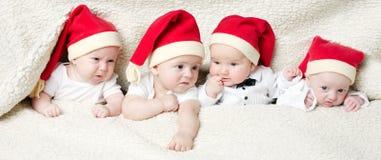 Cute babies with santa hats Stock Photo