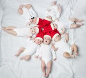 Cute babies with santa hats. On bright background stock photos