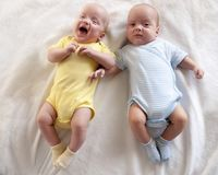 Cute babies twins boy and girl are lying on the bed and learn to keep your head. Cute babies twins boy and girl are lying on the bed and learn to keep your head royalty free stock photo